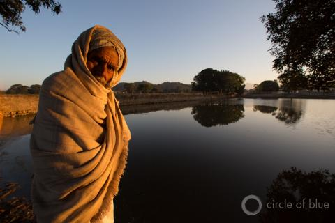 A man stands in front of a small lake in Punjab, India