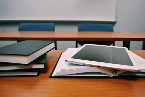 stack of books and a tablet on a desk
