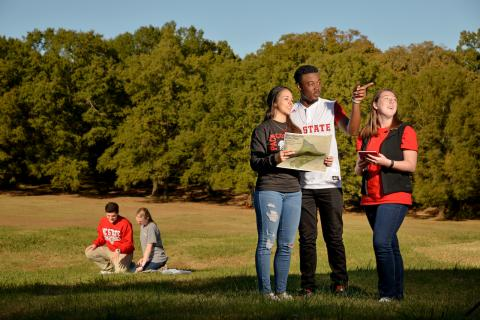 NC State students in a park area, looking at a map.
