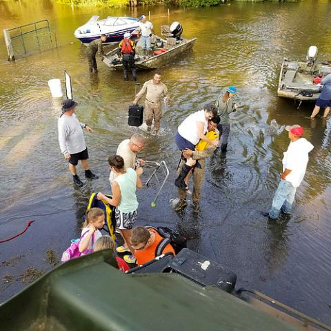 Rescuers evacuate people during a flood.